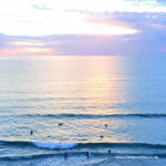 surfers catching the last waves before sunset on Watergate Bay beach near Newquay