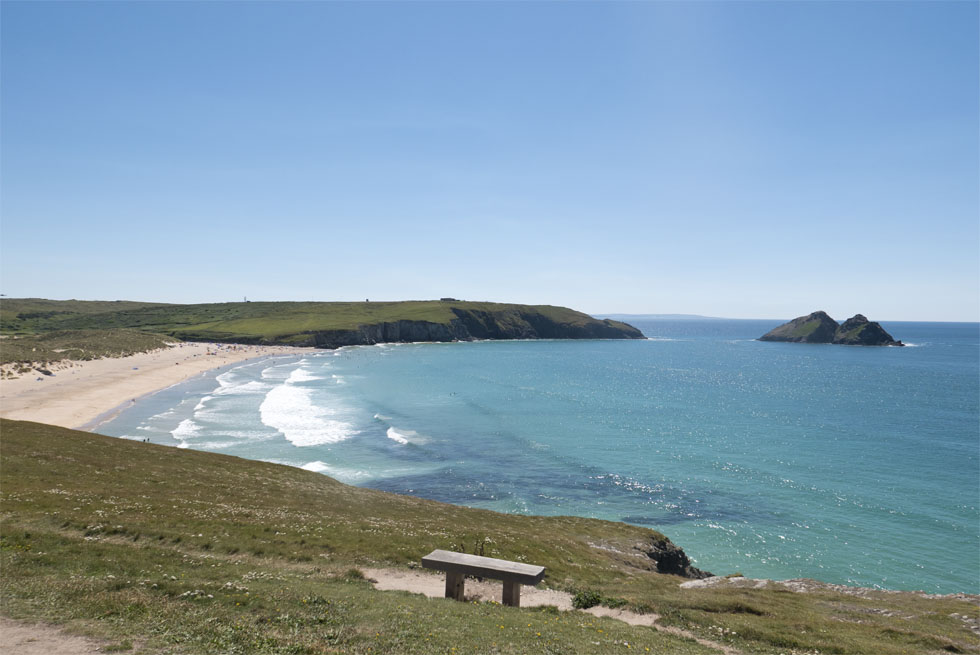 VIew of a bench overlooking Holywell Bay beach in Cornwall
